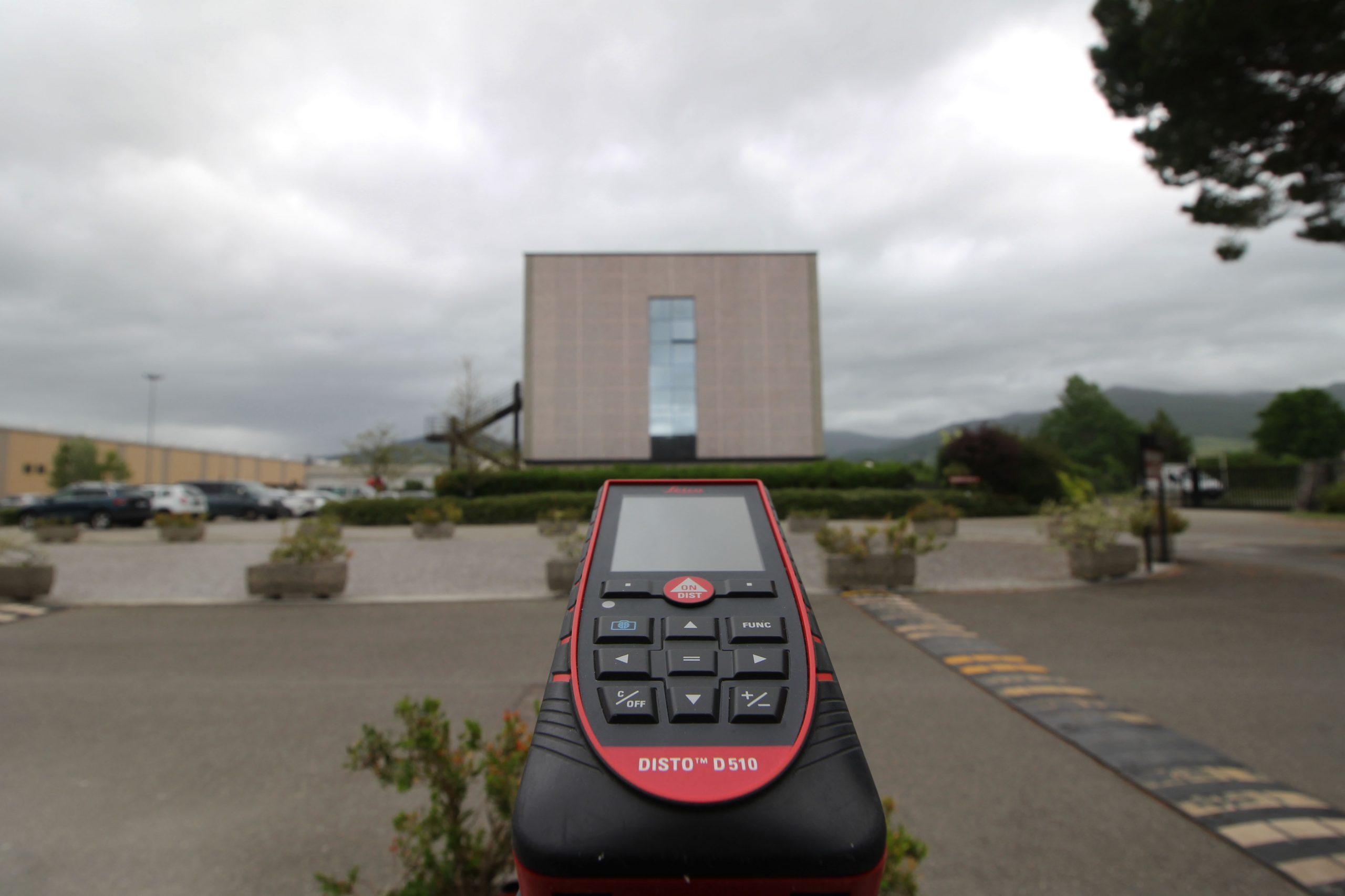 Strumento di rilevazione distanza e sullo sfondo la facciata di proiezione